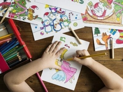 Child using colored pencils to draw several pictures.