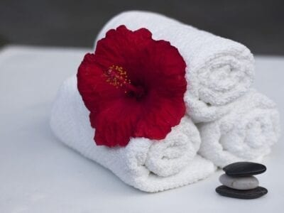 Three white hotel washcloths rolled up with a red hibiscus on them and three rocks stacked beside.