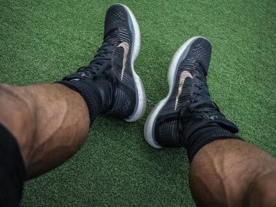 Close up photo of an athlete wearing black tennis shoes.