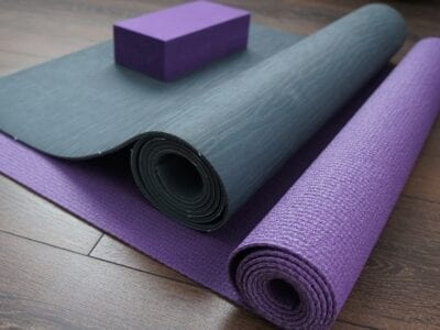 Photo of grey and purple exercise mats rolled up on floor.