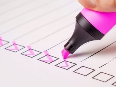 Close up photo of pink highlighter marking checks on a checklist.