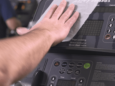 Photo of person's hand wiping gym equipment.