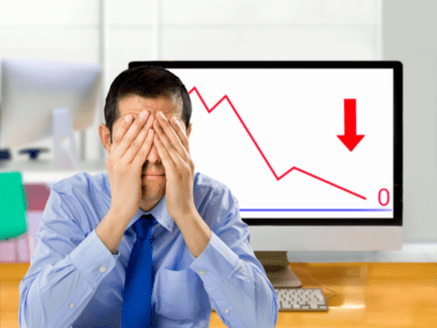 Photo young man with hands covering eyes and graph on computer screen showing negative results.