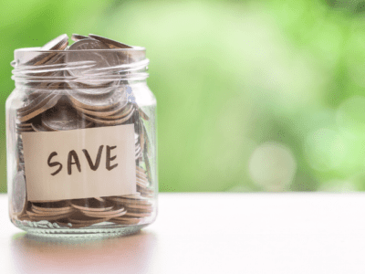 "Photo of glass jar filled with coins with label that says ""save."""