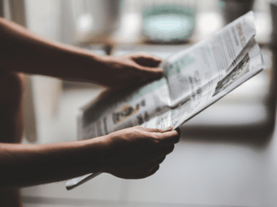 Close up photo of hands holding a newspaper.