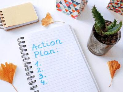 "Photo of lined paper with ""Action Plan"" written on it, a pen, small cactus and dried ginkgo leaves."