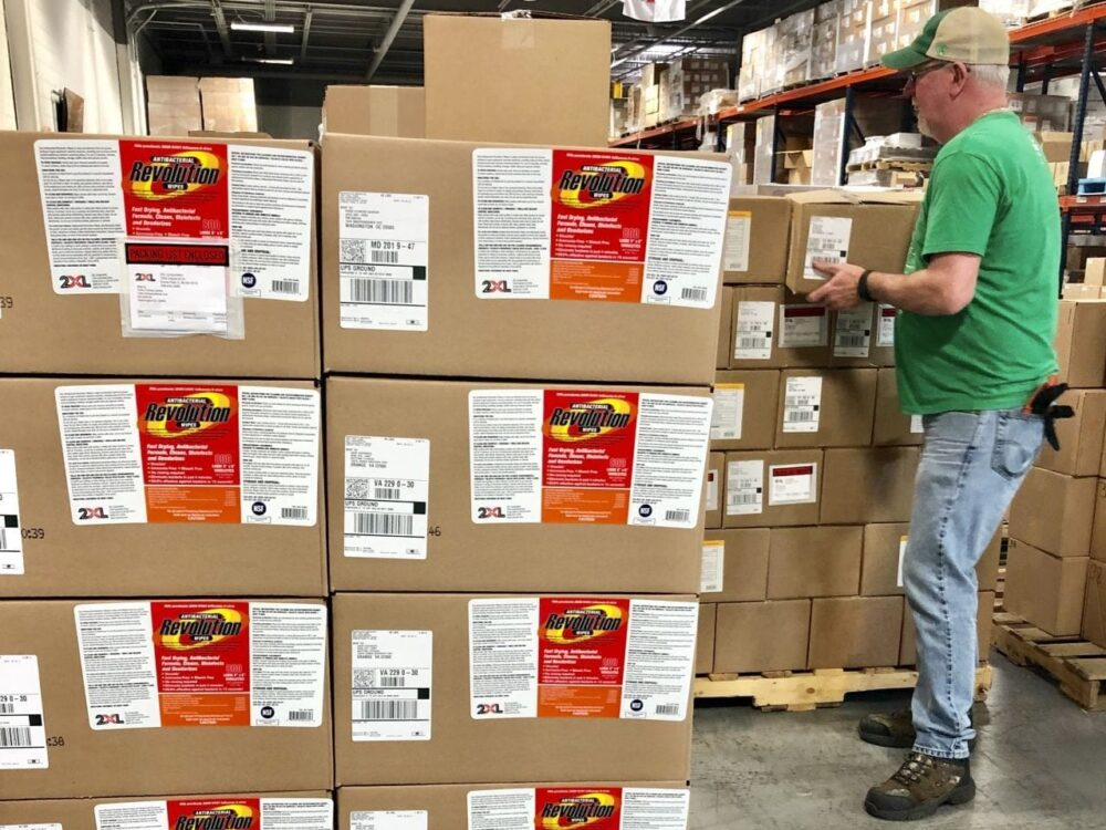 Man unloading boxes on pallet in a warehouse.
